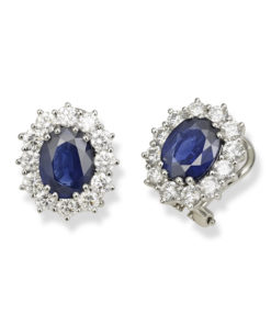Entourage earrings in white gold with deep blue oval sapphires surrounded by round diamonds makes a colorful statement.